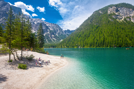 sudtirol: LAKE BRAIES, ITALY - JUL 03, 2015: Tourists walking at Lake Braies in the Dolomites with the Seekofel mountain in the background, Sudtirol,Italy Editorial