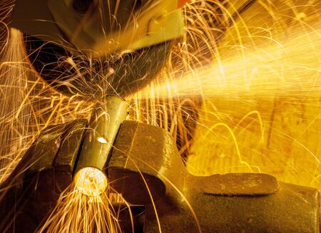 steel worker: Angle grinder working on a metal tube clamped in a vise. Stock Photo