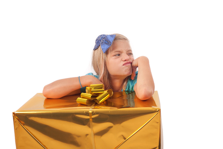 spite: Spoiled child with gift box. She is very unhappy in spite of she just got a big present. Stock Photo