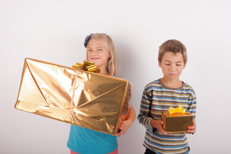 bother: Siblings comparing their presents. The girl is happy with a big gift box while her bother having a small one is very upset.