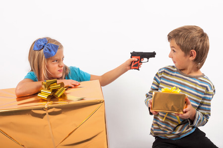 envious: Envious sister with big present box holding a toy gun to her brother holding a small gift box.