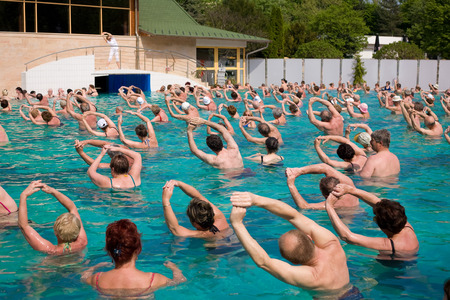 aerobic exercise: Harkany, Hungary - April 4, 2011: Group of people doing exercises in a thermal pool following a woman trainers instructions Editorial
