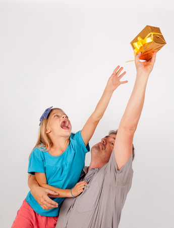girl fighting: Small girl fighting for a gift box with her dad. The father holding the small present box above his head
