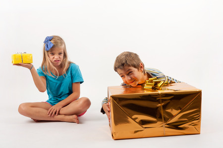 unfair: Unfair gift giving between siblings: the boy with big present box is happy but his sister is very upset because she has a very small one. Isolated on white.
