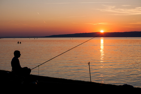 bather: Silhouette of a fisherman with his fisher rod at lake Balaton at sunset.