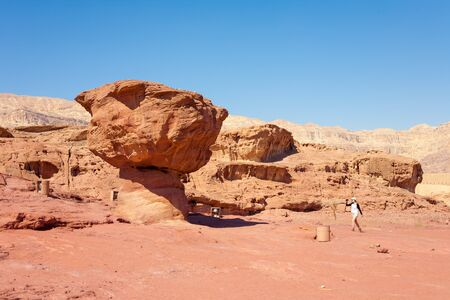timna: Young tourist woman taking photos of the Mushroom sandstone attraction of Timna Park, Israel