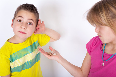 hist: Small boy cant hear - hist sister shows a hearing aid on her palm for him
