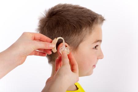 chico lindo que consigue su primer audífono Foto de archivo