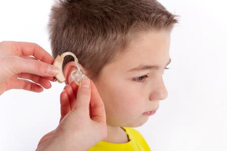 Hand inserting a hearing aid in an ear of a cute boy