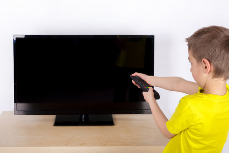 young boy turning off the television