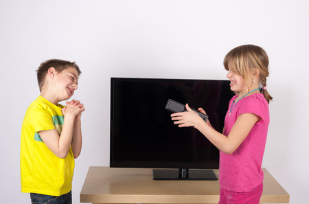 sibling rivalry: Siblings arguing in front of the TV - the brother begging for the remote control.