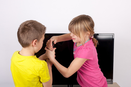sibling rivalry: Sibling fighting for the remote control in front of the television. Stock Photo