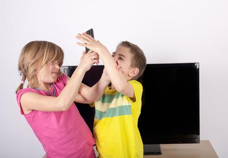 Rodzeństwo kłócą pilotem przed telewizorem.