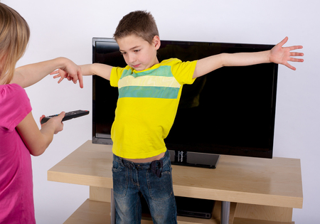 sibling rivalry: Small boy with arms wide open trying to prevent his sister to turn the TV on.