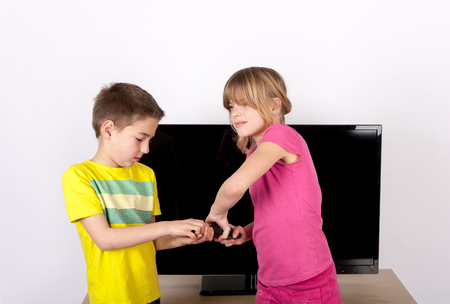 sibling rivalry: Sibling arguing over the remote control in front of the TV. Stock Photo