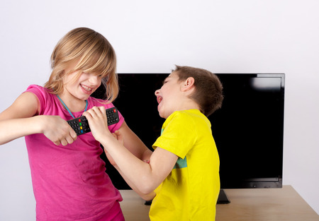 sibling rivalry: Girl and boy siblings fighting over the remote control in front of the television