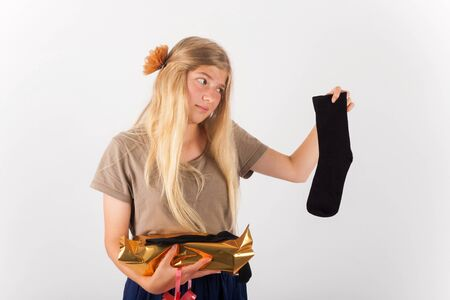 unwanted: Bad gift concept - Beautiful girl not happy with her present she got: a pair of socks.. Stock Photo