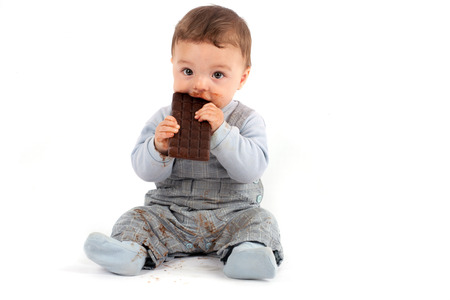 Adorable baby eating a plate of chocolate. Studio isolated on white background.