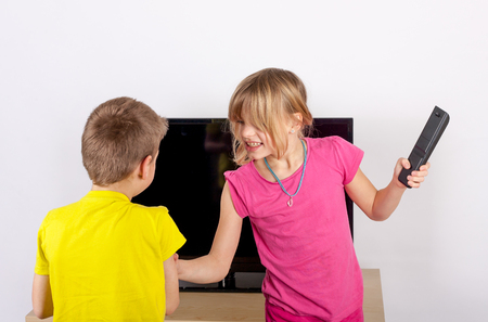brother sister fight: Siblings arguing over the remote control in front of the television. Stock Photo