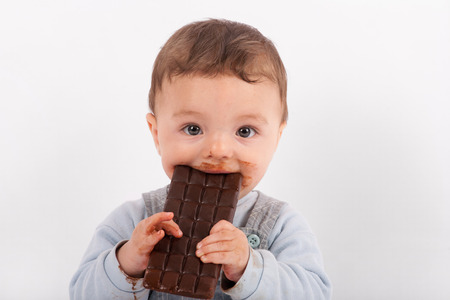 Cute baby eating a plate of chocolate Stok Fotoğraf