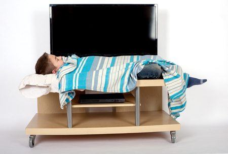 couch potato: TV addiction in childhood - young boy sleeping in front of the TV Stock Photo
