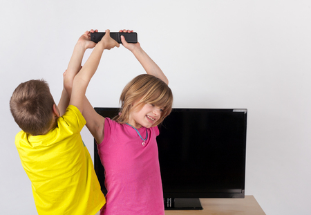 sibling rivalry: Little boy fighting with his sister for the remote control in front of the TV
