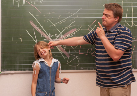 Angry teacher man pulling a naughty girls ear in front of the chalkboard.