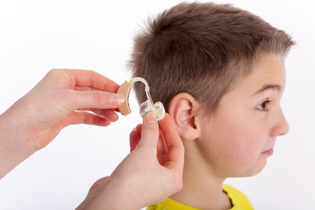 impaired: Audiologists inserting a hearing aid into a young boys ear. Focused on the hand and the hearing aid.