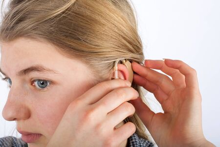 inserting: Close up of a deaf young womans ear when she inserting her hearing aid into ear