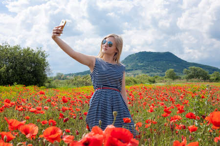 field stripped: Young girl wearing sunglasses and blue stripped cloth taking a selfie in a poppy field Stock Photo