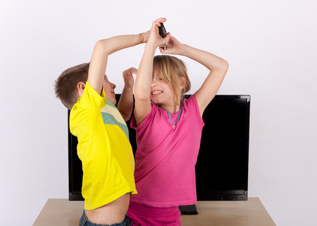 Kids fighting for the remote control in front of the TV Stock Photo