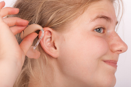 in insert: Portrait of a young woman trying to insert a hearing aid into ear Stock Photo
