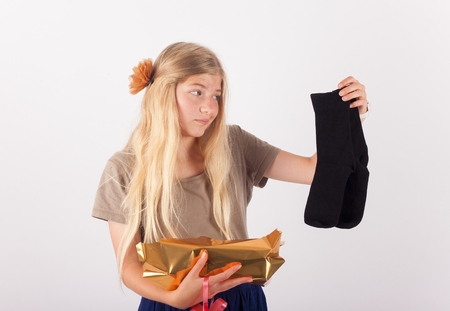 Girl unpacked her present and a bit upset because it was a pair of black socks only. Stock Photo