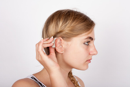 inserting: Portrait of a beautiful girl inserting a hearing aid in her ear Stock Photo