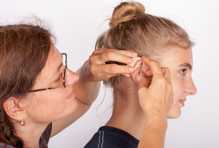 Audiologist fitting a young woman patient with a behind-the-ear hearing aid Stock Photo
