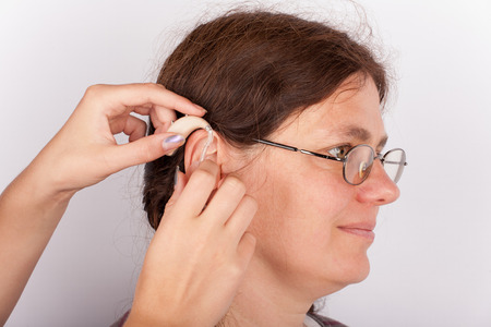 int: Audiologists hands inserting a hearing aid int an ear of a woman
