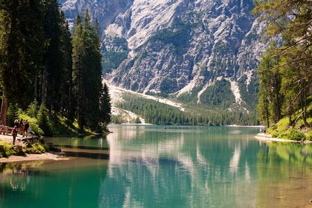 sudtirol: LAKE BRAIES, ITALY - JUL 03, 2015: Tourists walking around the Lake Braies in the Dolomites with the Seekofel mountain in the background, Sudtirol,Italy Editorial