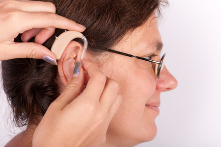 close fitting: Close up of hands fitting a woman with hearing aid