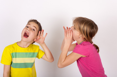 he   my sister: Boy cupping his hand behind ear because he cant hear his sister voice Stock Photo