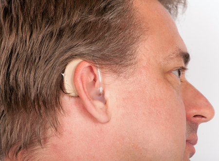 using senses: Close up ear of a senior man wearing hearing aid