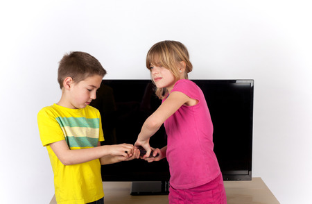 sibling rivalry: Girl and boy siblings arguing over the remote control in front of the TV