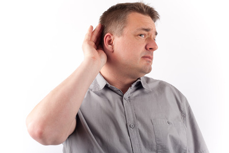 Senior man cupping hand behind ear trying to hear