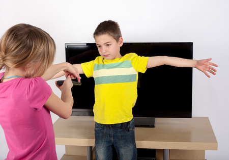 sibling rivalry: Do not turn the TV on - Girl trying to set the TV on with the remote control while her brother blocking it