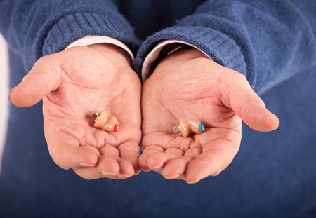 completely: Senior mans hand showing a CIC (completely in canal)  hearing aids left and right Stock Photo