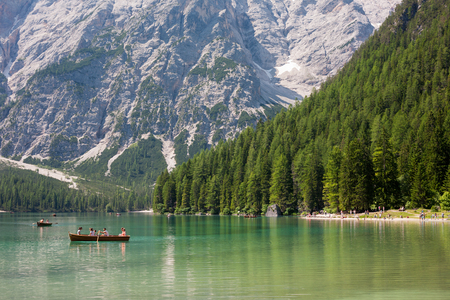 LAKE BRAIES, ITALY - JUL 03, 2015: Tourists boating at Lake Braies in the Dolomites with the Seekofel mountain in the background, Sudtirol,Italy