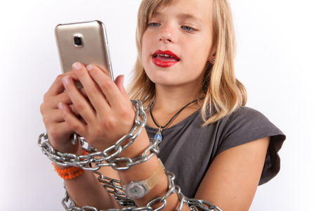 Internet addiction concept - Young girl shackled with a chain using smartphone.
