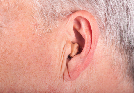 Close-up of a senior man's ear wearing a small hearing aid photo