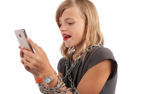 girl tied: Mobile addiction - Young girl tied with a chain using smartphone. Isolated on white. Stock Photo