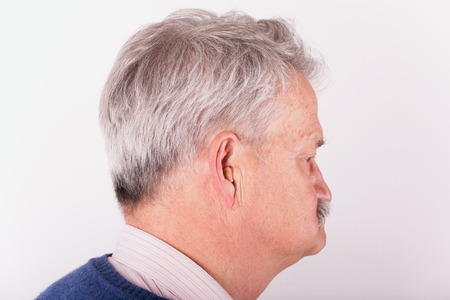 Portrait of a senior man wearing a small CIC (Completely in Canal) hearing aid photo