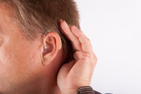 using senses: Close up ear of a man wearing hearing aid  cupping his hand behind his ear Stock Photo